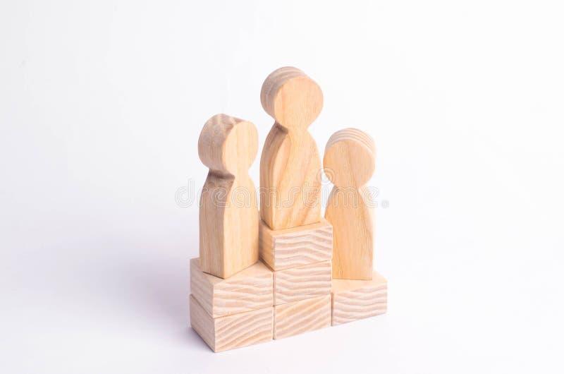 Tres figuras de madera de un hombre se colocan en el podio de los ganadores El concepto de victoria, de competencia del negocio y fotos de archivo