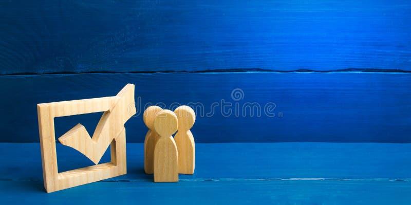 Tres figuras humanas de madera se unen al lado de una se?al en la caja El concepto de elecciones y de tecnolog?as sociales volunt fotografía de archivo