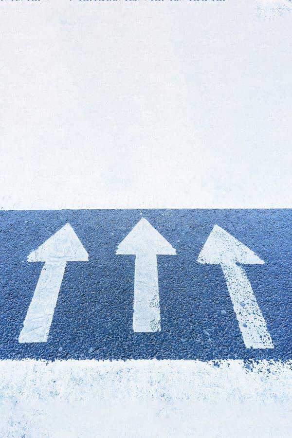Tres flechas en la superficie azul del destacar del asfalto, adelante imagen de archivo