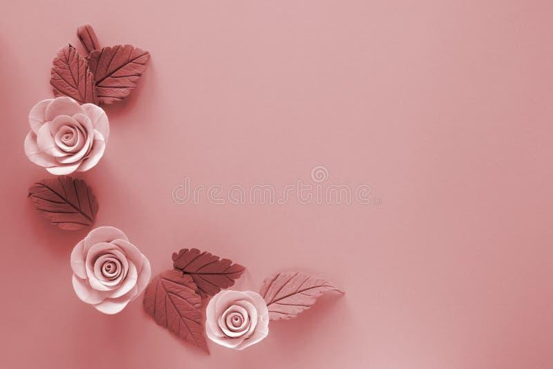 Tres flores color de rosa artificiales amarillas claras con las hojas en fondo coralino de vida Espacio libre para añadir el text imagenes de archivo