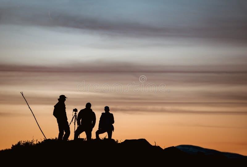 Tres fotógrafos que toman la foto contra puesta del sol foto de archivo