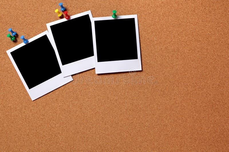 Tres fotos en blanco fijadas a un tablero del corcho imágenes de archivo libres de regalías