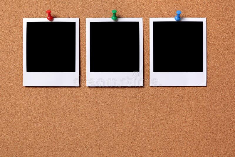 Tres fotos en blanco fijadas a un tablero del corcho fotografía de archivo