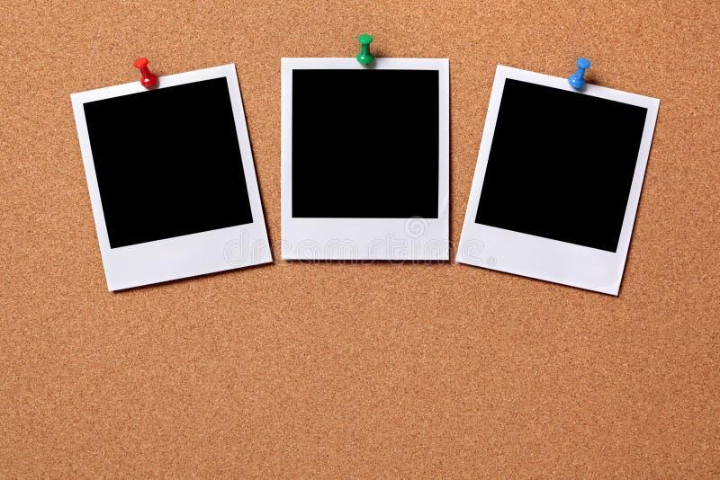 Tres fotos en blanco fijadas a un tablero del corcho fotos de archivo libres de regalías