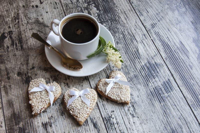 Tres galletas que se casaban adornaron el sésamo blanco con una taza de café. Estilo retro. fotografía de archivo libre de regalías