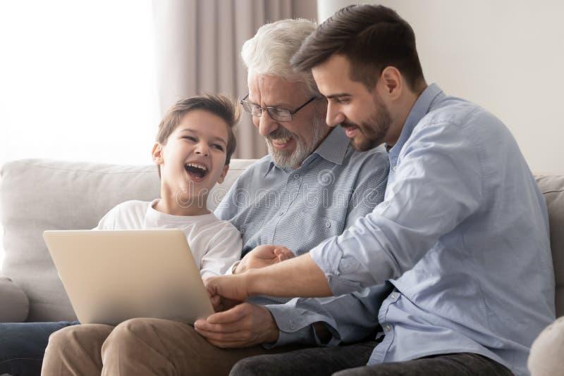 Tres generaciones de hombres se relajan en casa con el ordenador port?til imágenes de archivo libres de regalías