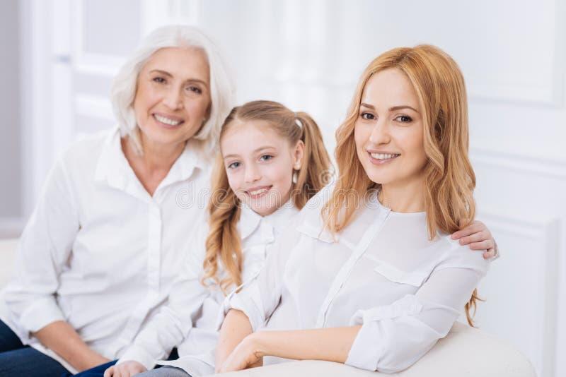 Tres generaciones de la familia que descansa sobre el sofá foto de archivo libre de regalías