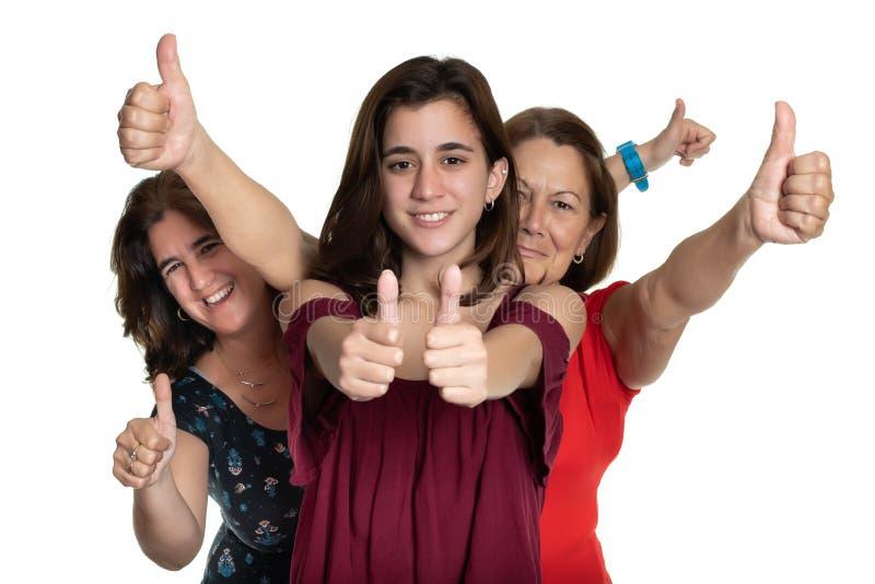 Tres generaciones de mujeres latinas que sonríen y que hacen los pulgares encima de la muestra - en un fondo blanco imagen de archivo
