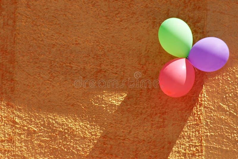 Tres globos coloridos del partido y pared textured anaranjada imágenes de archivo libres de regalías