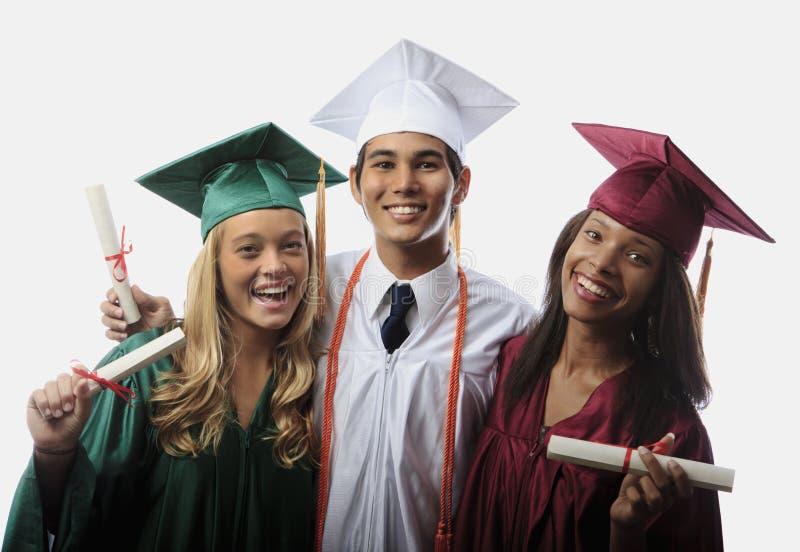 Tres graduados en casquillo y vestido imagenes de archivo
