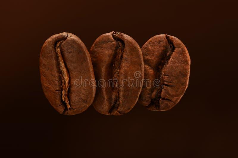 Tres granos de café asados frescos en un fondo marrón Ci?rrese para arriba, macro Postal, bandera imagen de archivo libre de regalías