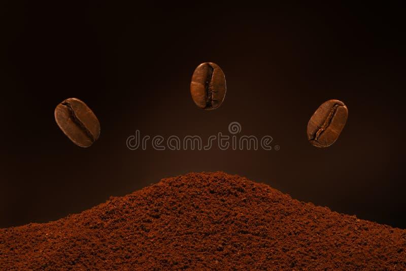 Tres granos de café asados frescos vuelan sobre un puñado de café molido en un fondo marrón Postal, bandera foto de archivo libre de regalías
