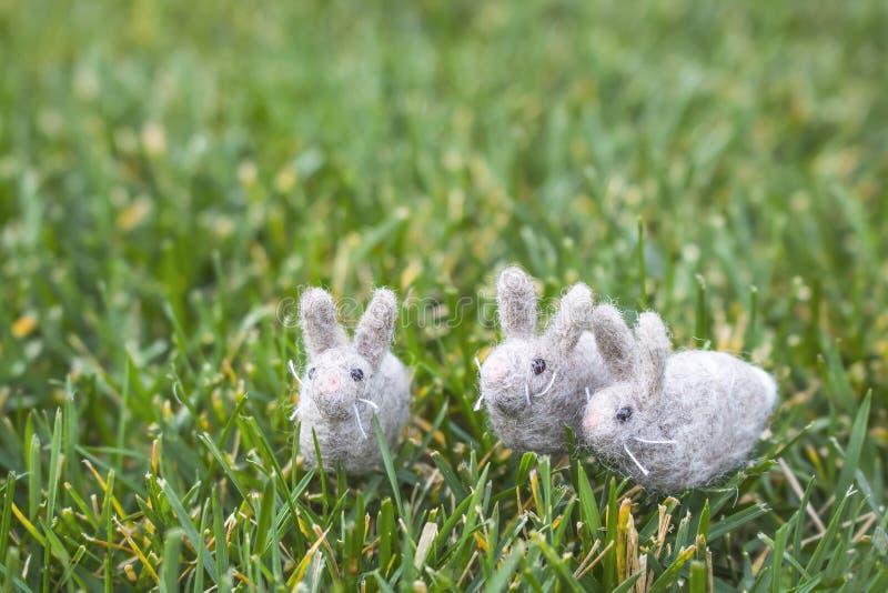 Tres Gray White Felted Rabbits o conejitos minúsculos en hierba verde fotografía de archivo