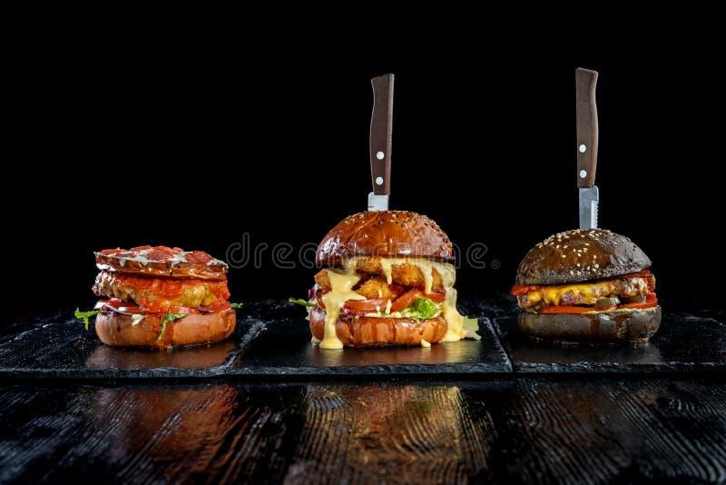 Tres hamburguesas con las entrerroscas, los anillos de cebolla, la chuleta de la carne de vaca y las pepitas de pollo foto de archivo libre de regalías