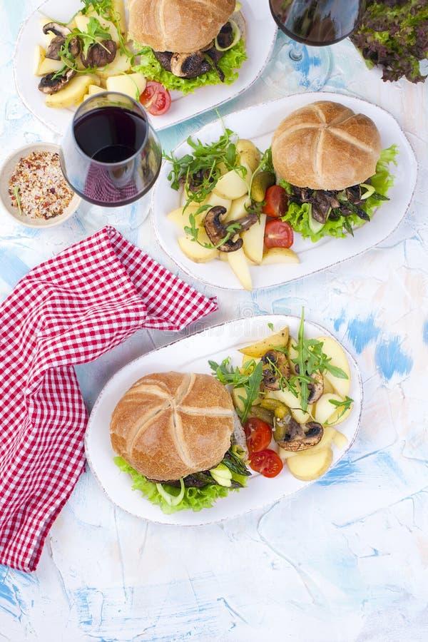 Tres hamburguesas grandes con la ensalada y las patatas Un vidrio de vino rojo Cena sabrosa Junk Food Texto, imágenes de archivo libres de regalías