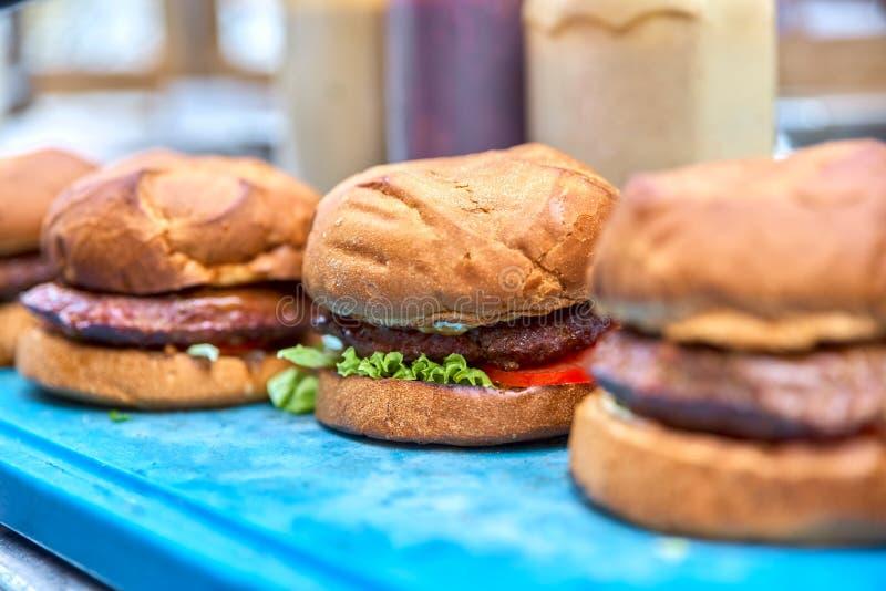 Tres hamburguesas Solamente prigatovleny y mentira en el lugar de trabajo fotografía de archivo libre de regalías