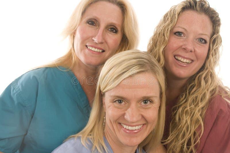 Tres hembras médicas de las enfermeras con la expresión feliz foto de archivo