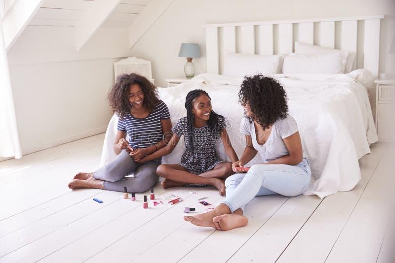 Tres hermanas adolescentes que se dan cambio de imagen en dormitorio foto de archivo libre de regalías
