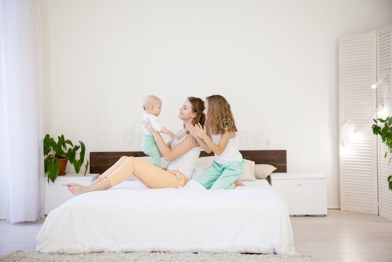 Tres hermanas de las muchachas en el juego en el dormitorio en el amor de la mañana foto de archivo libre de regalías