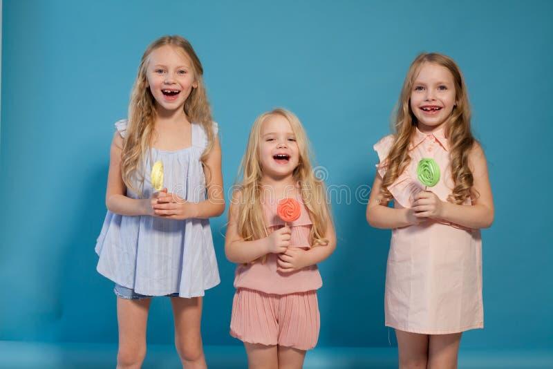 Tres hermanas de las novias comen la piruleta dulce con el postre del chocolate dulce fotos de archivo