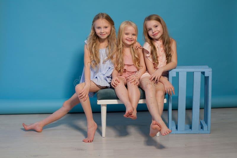 Tres hermanas de moda de las novias de las muchachas comen la torta de la piruleta del caramelo fotografía de archivo