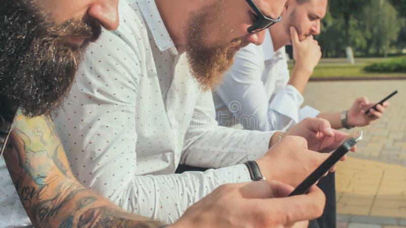 Tres hombres barbudos brutales utilizan sus teléfonos imagenes de archivo