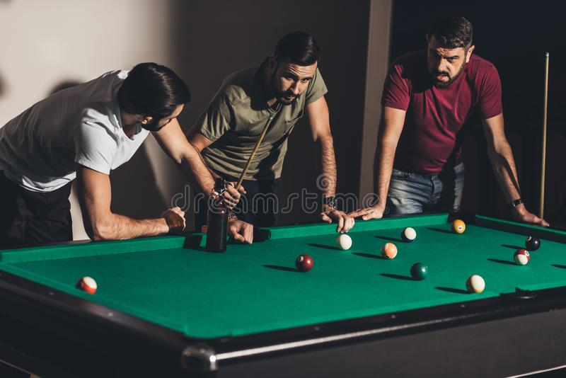 tres hombres caucásicos hermosos que juegan en billar foto de archivo libre de regalías