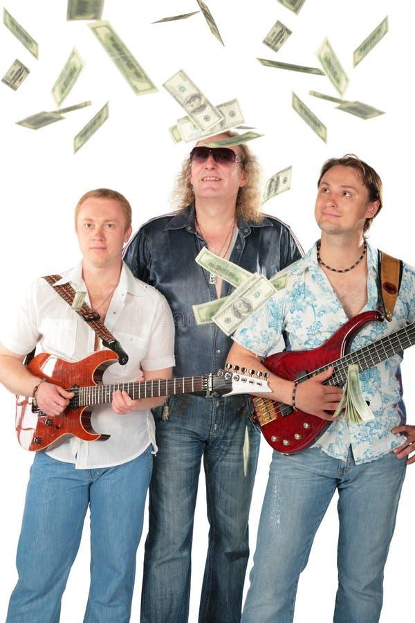 Tres hombres con dos guitarras y dólares que caen. M imagen de archivo libre de regalías
