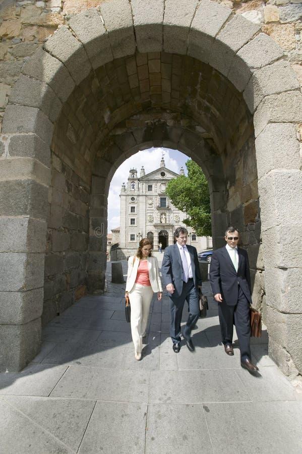 Tres hombres de negocios caminan a través de la puerta de la ciudad emparedada, Ávila España, un pueblo español castellano viejo fotos de archivo