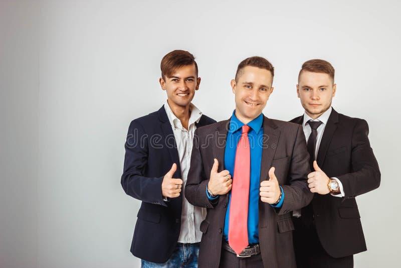 Tres hombres de negocios en los trajes que se colocan como un equipo imágenes de archivo libres de regalías