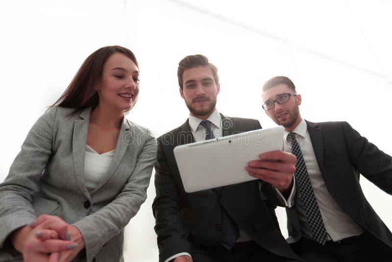 Tres hombres de negocios están mirando una tableta imagen de archivo libre de regalías