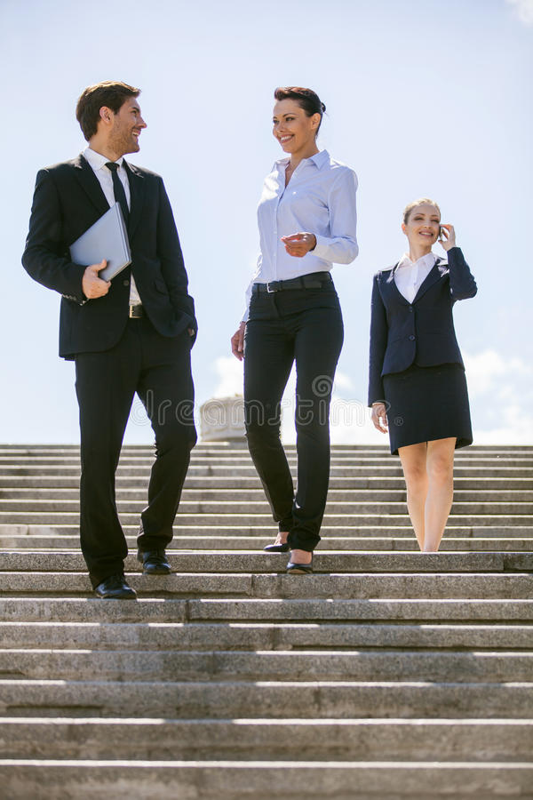 Tres hombres de negocios felices que caminan junto afuera imagen de archivo libre de regalías
