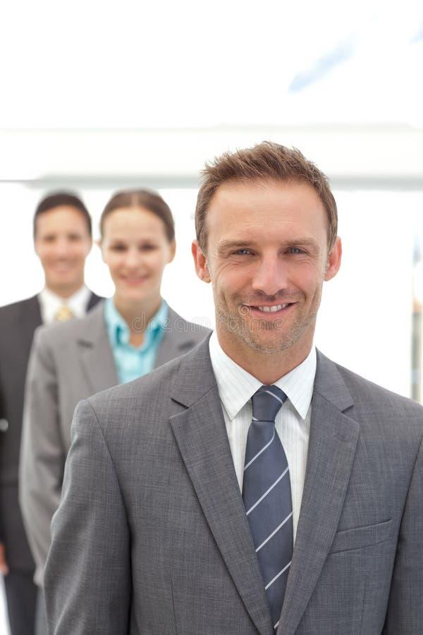 Tres hombres de negocios felices que presentan en una fila imagen de archivo libre de regalías