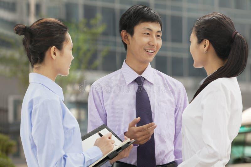 Tres hombres de negocios jovenes que hablan y que sonríen al aire libre, Pekín fotografía de archivo
