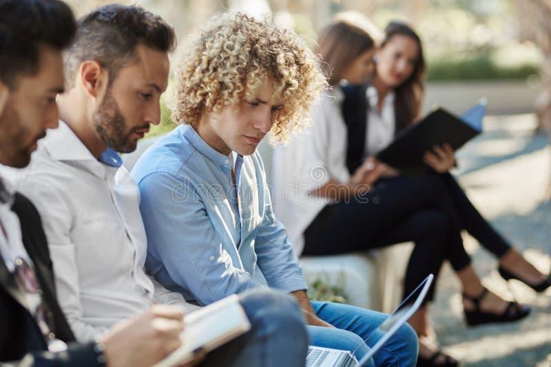 Tres hombres de negocios que se sientan afuera usando el ordenador portátil imagen de archivo