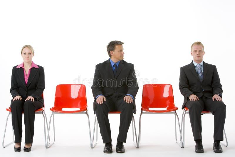 Tres hombres de negocios que se sientan en asientos plásticos rojos fotografía de archivo libre de regalías