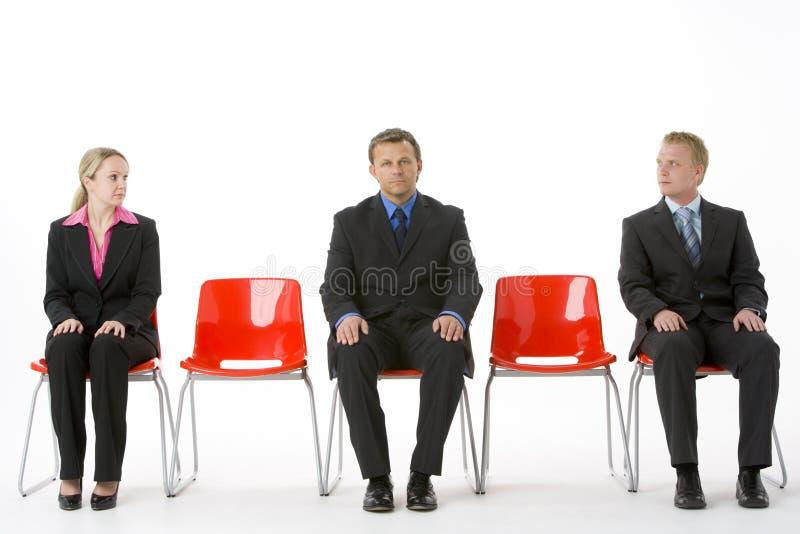 Tres hombres de negocios que se sientan en asientos plásticos rojos foto de archivo