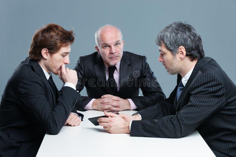 Tres hombres de negocios que tienen una discusión seria imágenes de archivo libres de regalías