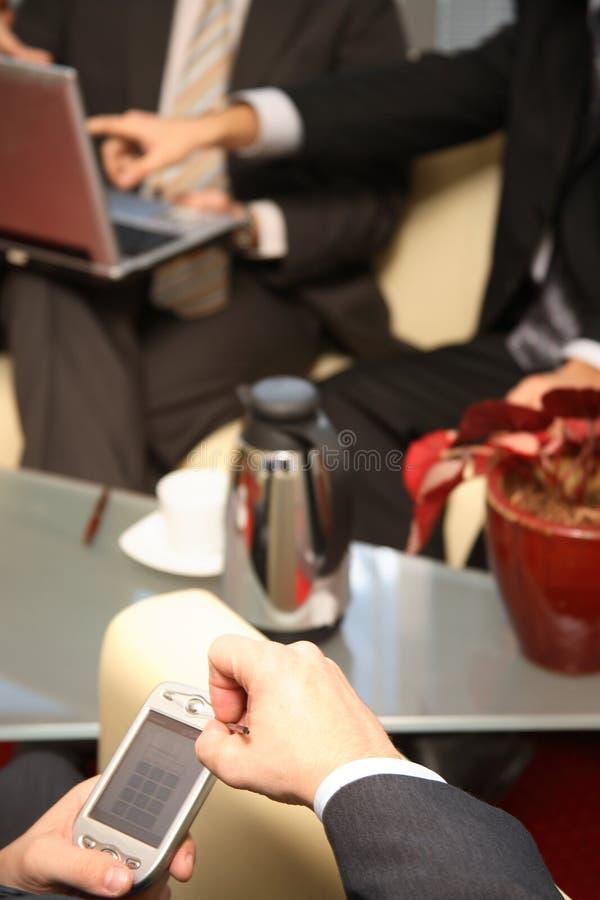 Tres hombres de negocios que trabajan en los dispositivos electrónicos - ascendente cercano imagenes de archivo