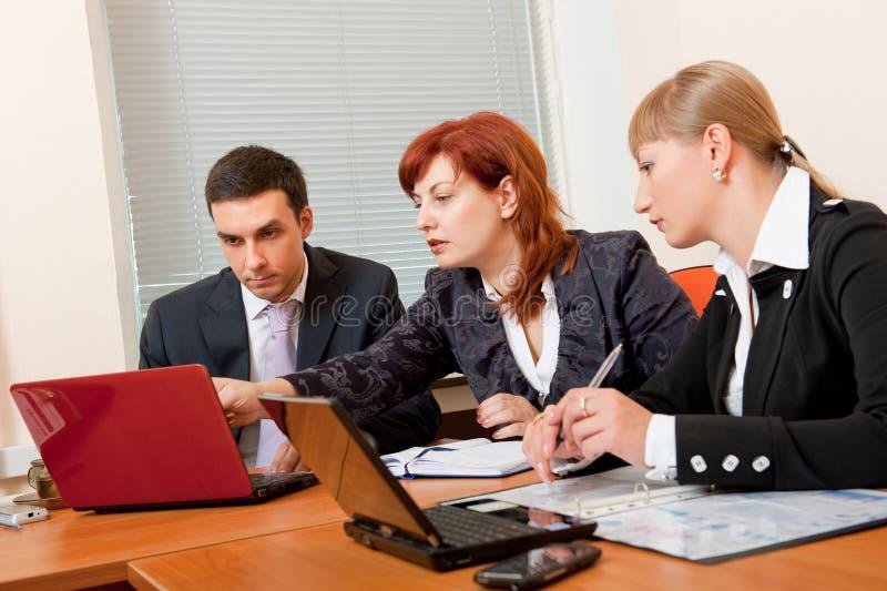 Tres hombres de negocios se están reuniendo foto de archivo