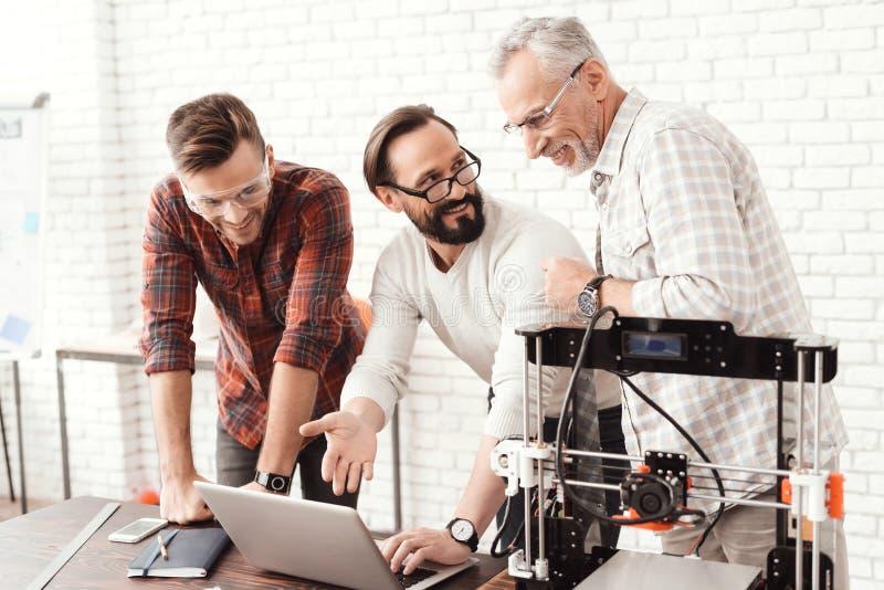 Tres hombres están trabajando en la preparación de una impresora 3d para imprimir Uno de ellos explica el resto de la delicadeza  foto de archivo libre de regalías