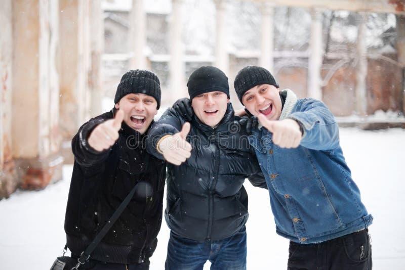 Tres hombres jovenes felices que muestran el pulgar para arriba imagen de archivo
