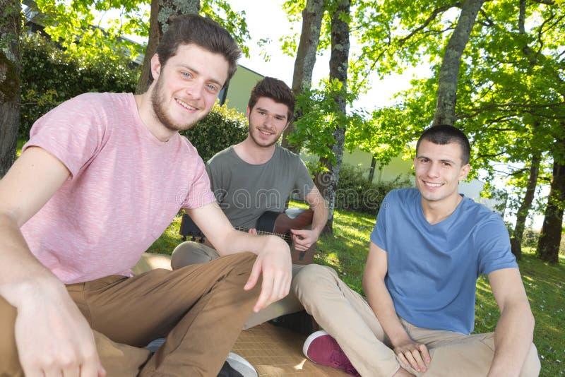 Tres hombres jovenes sentados en hierba imagen de archivo libre de regalías