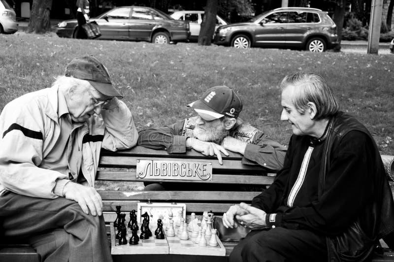 Tres hombres que juegan a ajedrez fotografía de archivo