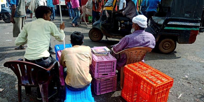 Tres hombres que miran actividades del mercado en el mercado de los granjeros foto de archivo libre de regalías