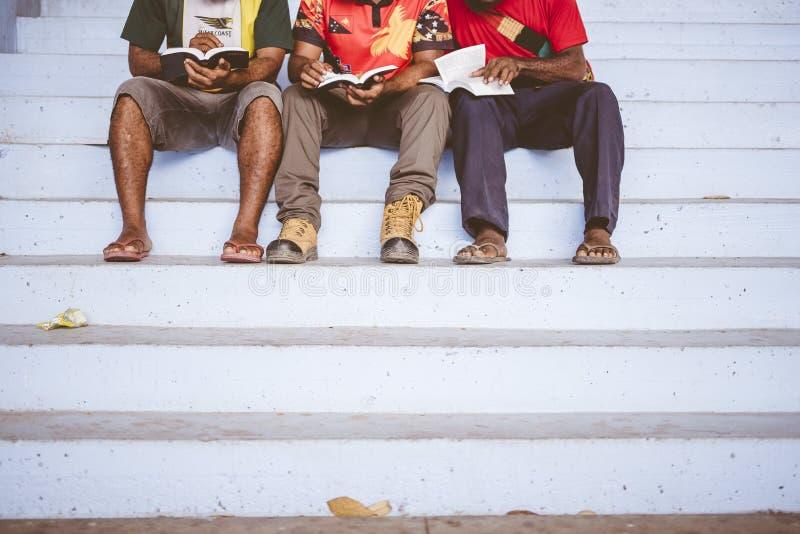 Tres hombres sentados en la escalera uno al lado del otro mientras leen la Biblia fotos de archivo