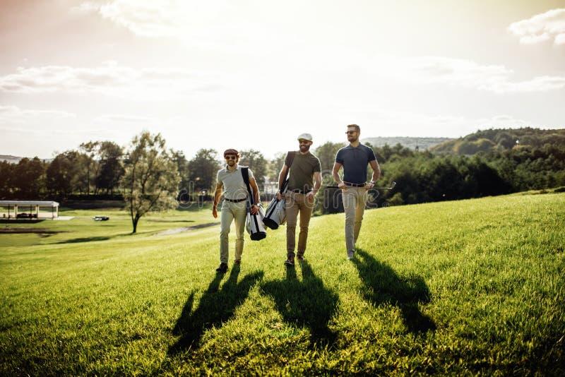 Tres hombres sonrientes en las gafas de sol que detienen a los clubs de golf al aire libre foto de archivo libre de regalías