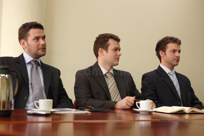 Tres hombres y una conferencia imagenes de archivo