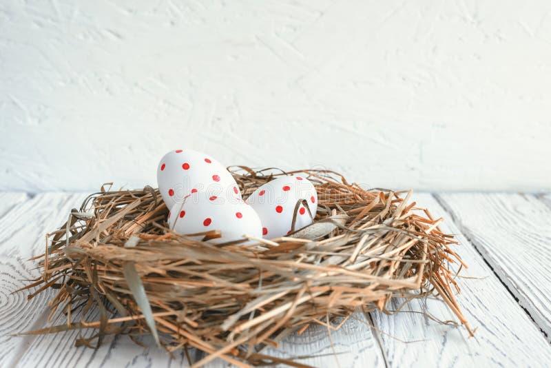 Tres huevos con los puntos rojos en un día de fiesta de Pascua de la jerarquía del heno fotos de archivo