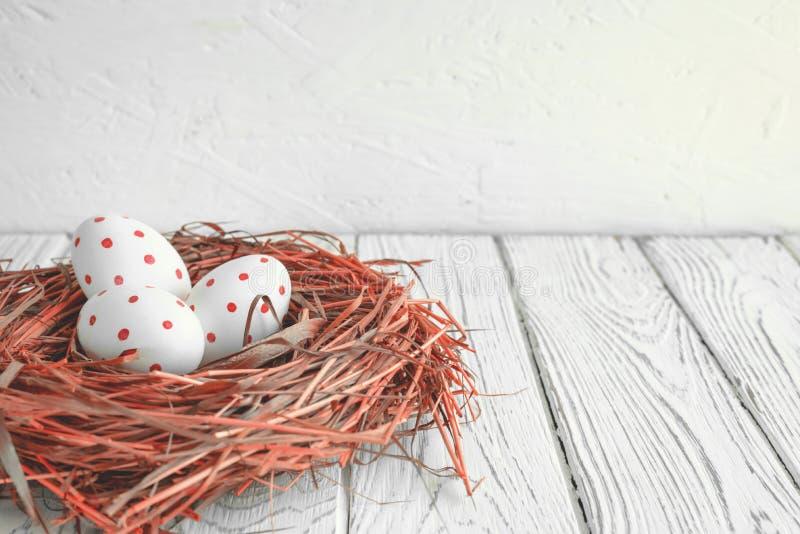 Tres huevos con los puntos rojos en un día de fiesta de Pascua de la jerarquía del heno fotografía de archivo libre de regalías